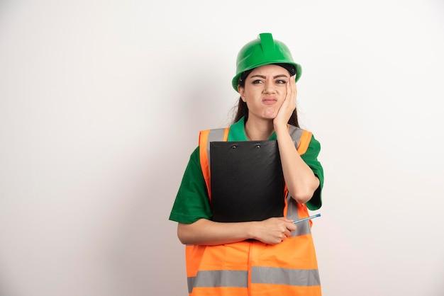 Portret zmęczonej kobiety kierownik nieruchomości ze schowkiem. zdjęcie wysokiej jakości