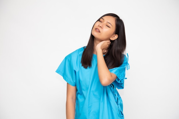 Portret zmęczonej młodej azjatyckiej kobiety w niebieskim garniturze pacjenta z bólem szyi na białym tle