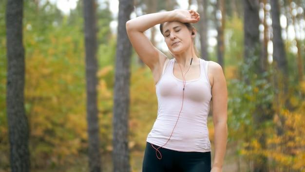 Portret zmęczonej młodej kobiety dotykając czoła po joggingu w lesie lub parku.