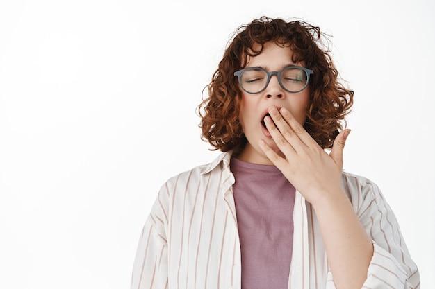 Portret zmęczonej młodej studentki. kręcona programistka ziewa w okularach, czuje się śpiąca lub znudzona, ziewa ręką, stoi na białym