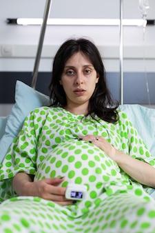 Portret zmęczonej osoby w ciąży siedzącej w łóżku na oddziale szpitalnym