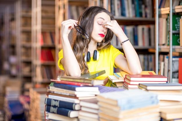 Portret zmęczonej studentki studiującej z książkami w bibliotece