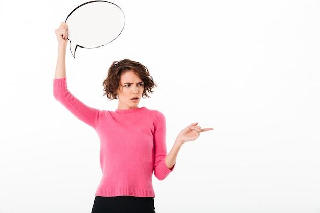 Portret zmieszana ładna dziewczyna trzyma pustego mowa bąbel