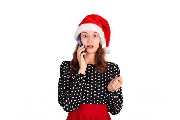 Portret zmieszana śliczna dziewczyna w smokingowej rozmowie przy telefonem komórkowym. emocjonalna dziewczyna w santa claus bożego narodzenia kapeluszu odizolowywającym