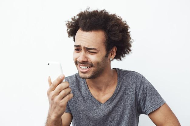 Portret zmieszanego, ale wesołego i przystojnego afrykańskiego mężczyzny uśmiechniętego, patrząc na telefon komórkowy, zaskoczony zdjęciem w mediach społecznościowych lub rozmową wideo.