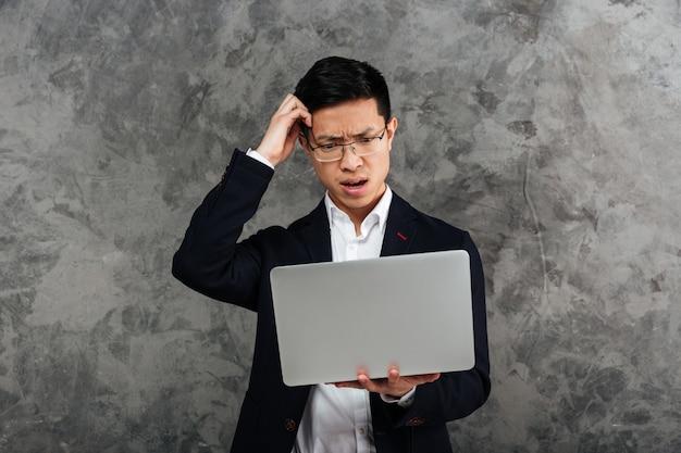 Portret zmieszany młody azjatykci mężczyzna ubierał w kostiumu