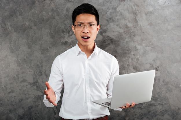 Portret zmieszany młody azjatykci mężczyzna ubierał w koszula