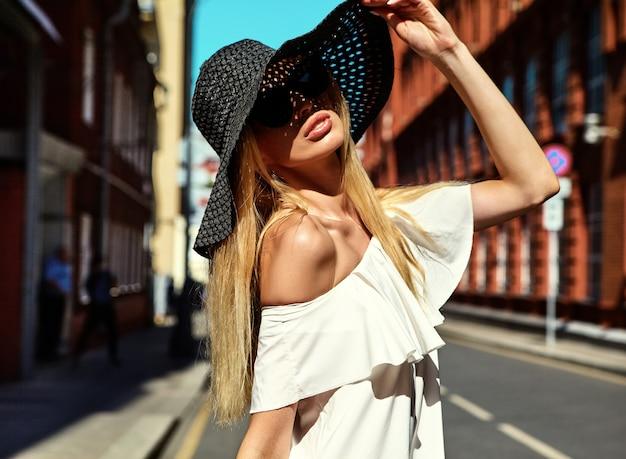 Portret zmysłowa blondynki kobiety model ubierał w biel sukni i lato plażowym kapeluszu pozuje na ulicznym tle za zmierzchem