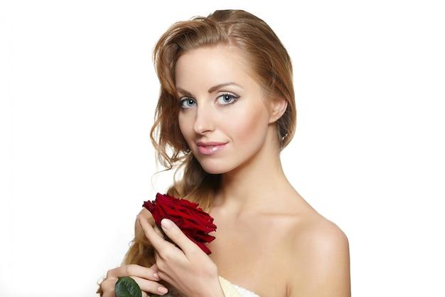 Portret zmysłowa piękna kobieta z czerwieni różą na bielu