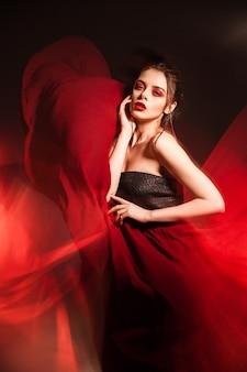 Portret zmysłowej atrakcyjnej modelki z makijażem w machającej czerwonej sukience. długa ekspozycja