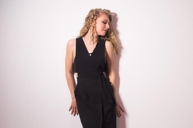 Portret zmysłowej blond kobiety z kręconymi włosami na jasnoszarym tle.