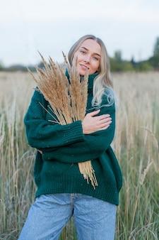 Portret zmysłowej blond młodej kobiety w pszenicy w letni wieczór.