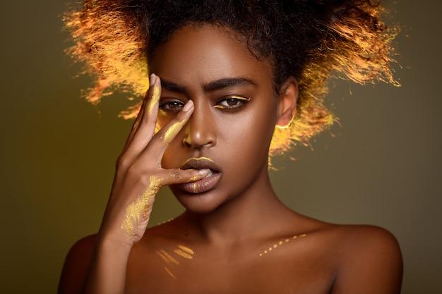 Portret zmysłowej kobiety afryki złotą farbą na twarzy i rękach.