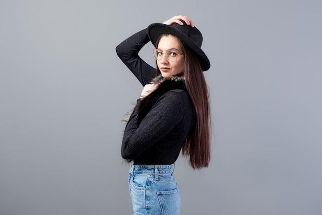 Portret zmysłowej kobiety z długimi włosami i czarnym kapeluszem na głowie na szarym tle