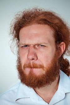 Portret zniesmaczonego mężczyzny o długich rudych włosach