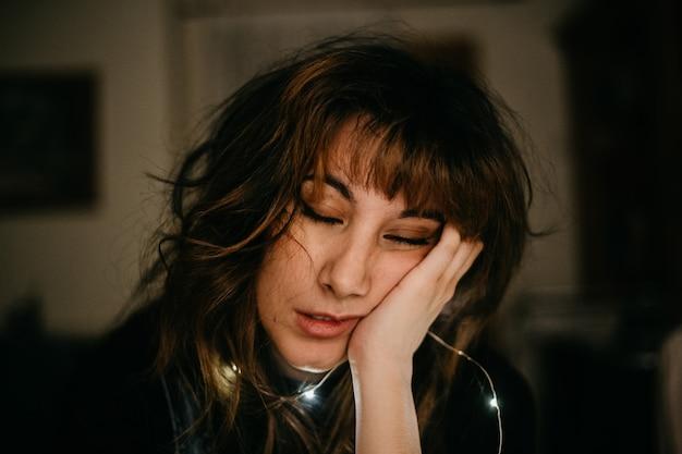Portret znudzona młoda kobieta z dowodzonymi światłami