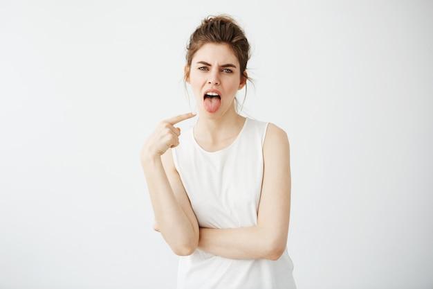 Portret znudzona niezadowolona młoda kobieta wskazuje palec przy jej jęzorem.