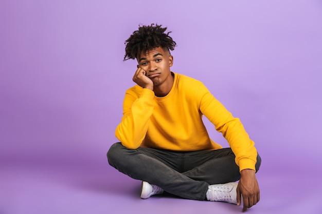Portret znudzonego afroamerykańskiego chłopca siedzącego na podłodze ze skrzyżowanymi nogami i podpierającego głowę, na białym tle nad fioletowym tłem