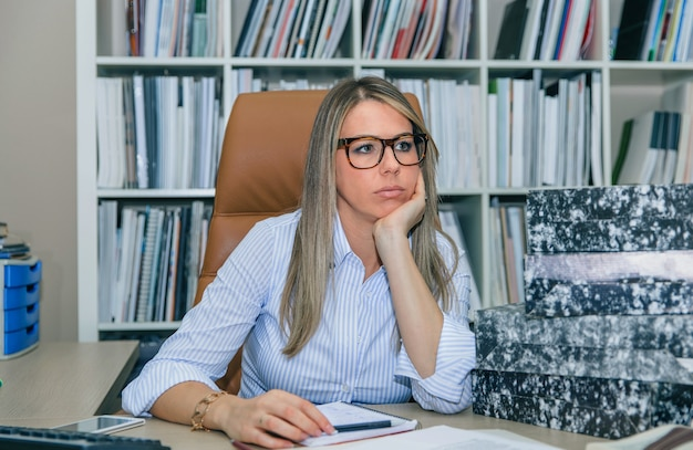 Portret znudzonej blond sekretarki z dużą ilością pracy czekającej na jej pulpicie