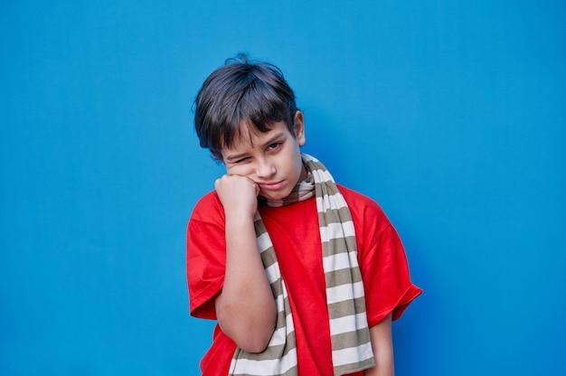 Portret znudzony chłopiec w czerwonej koszulce i szaliku