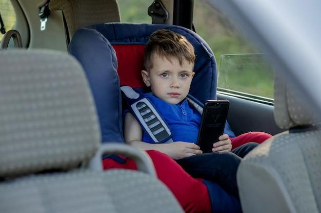 Portret znudzony mały chłopiec siedzi w foteliku samochodowym. bezpieczeństwo przewozu dzieci.