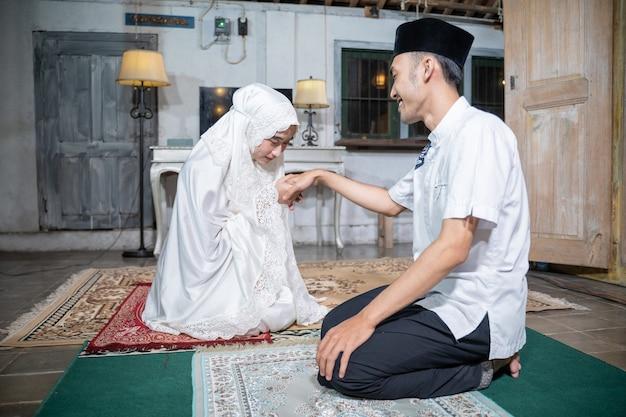 Portret żony całuje rękę męża po wspólnej modlitwie w domu. sholat lub salat