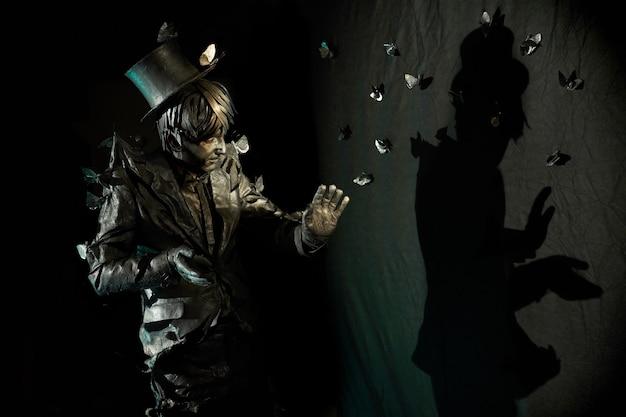 Portret zręcznego mima, którego wygląd przypomina posąg z brązu, gestykuluje i pokazuje jakąś postać swoim cieniem na czarnej ścianie. mężczyzna pantomimista podczas pracy w niemej komedii