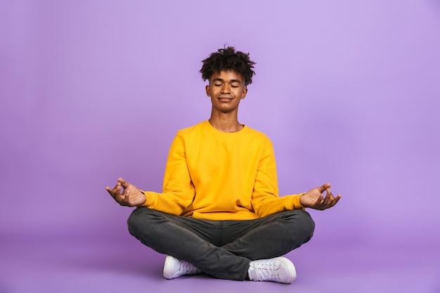 Portret zrelaksowanego afroamerykańskiego chłopca siedzącego w pozycji lotosu i medytującego z zamkniętymi oczami, odizolowanego na fioletowym tle