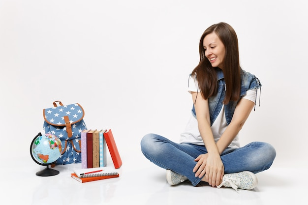 Portret zrelaksowanej, delikatnej, uśmiechniętej studentki w dżinsowych ubraniach, patrzącej w dół i siedzącej w pobliżu kuli ziemskiej, plecaka, podręczników szkolnych na białym tle