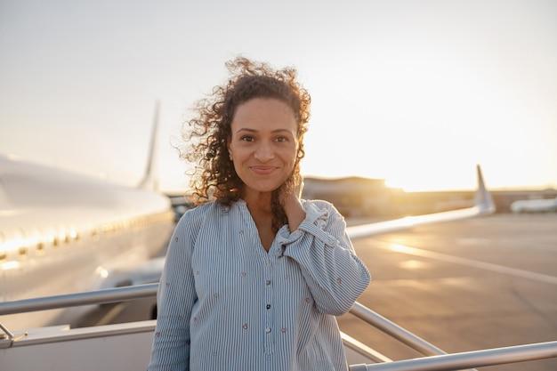 Portret zrelaksowanej kobiety uśmiecha się do kamery, stojąc na zewnątrz gotowy do wejścia na pokład samolotu o zachodzie słońca. wakacje, styl życia, koncepcja podróży