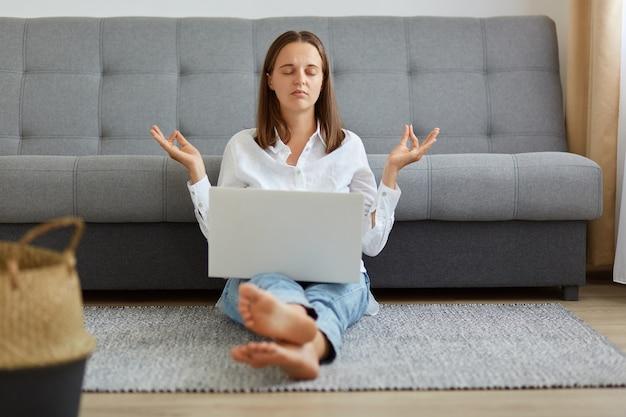 Portret zrelaksowanej kobiety w białej koszuli i dżinsach, siedzącej na podłodze z laptopem na nogach, trzymającej ręce w geście jogi, próbującej się uspokoić i odpocząć.