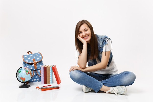 Portret zrelaksowanej uśmiechniętej studentki w dżinsowych ubraniach z podbródkiem na dłoni, siedzącej w pobliżu kuli ziemskiej, plecaka, podręczników szkolnych na białym tle