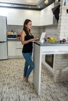 Portret zrelaksowany szczęśliwy dziewczyna w słuchawkach studiuje lub słucha muzyki w kuchni. styl życia zdrowia