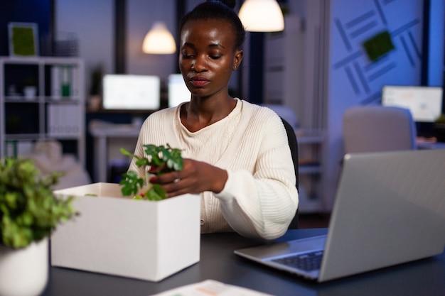 Portret zrezygnowanej zwolnionej afroamerykańskiej bizneswoman pakującej przedmioty