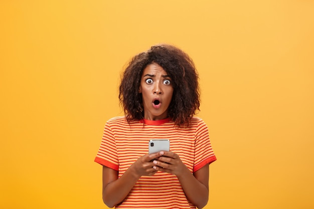 Portret zszokowana ciemnoskóra kobieta trzyma smartfon z fryzurą afro.