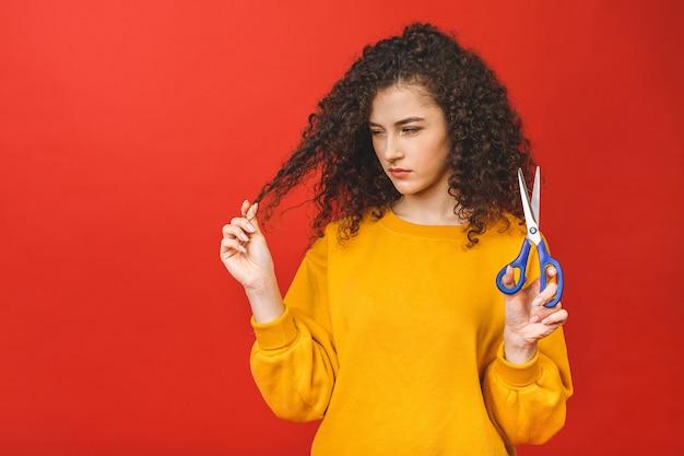 Portret zszokowana dziewczyna kręcone cięcie jej włosy nożyczkami, na białym tle na czerwonym tle.