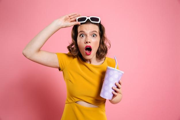 Portret zszokowana dziewczyna trzyma kubek w okularach przeciwsłonecznych