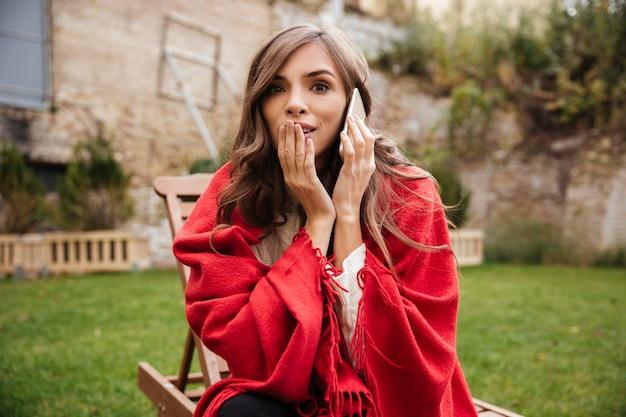 Portret zszokowana kobieta rozmawia przez telefon komórkowy