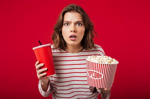 Portret zszokowana kobieta trzyma popcorn