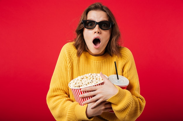 Portret zszokowana kobieta w okularach gospodarstwa popcorn