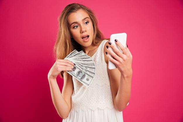 Portret zszokowana ładna dziewczyna trzyma banknoty pieniądze