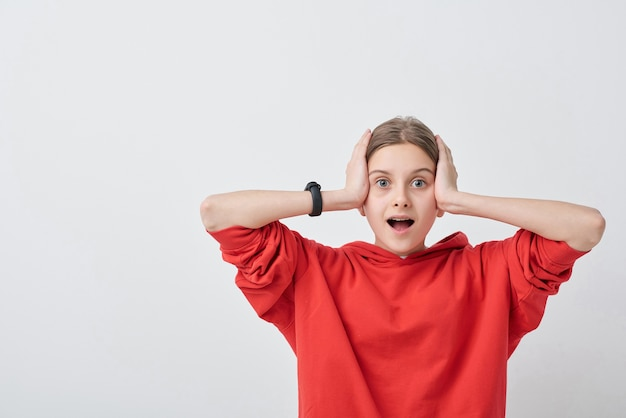 Portret zszokowana nastolatka w czerwonej bluzie z kapturem, trzymając usta otwarte i trzymając głowę w dłoniach