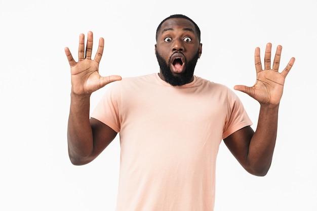 Portret zszokowanego afrykańskiego mężczyzny ubranego w t-shirt stojący na białym tle nad białą ścianą, gestykulujący