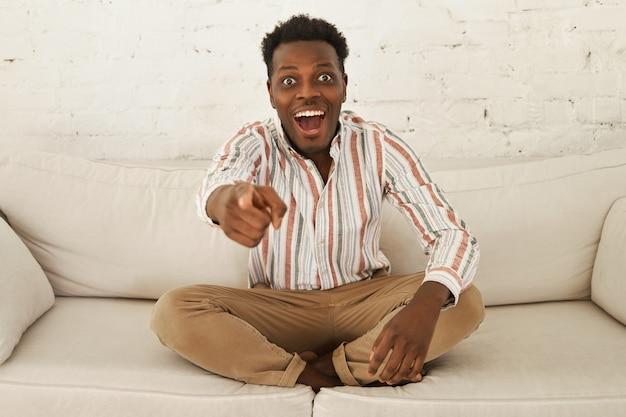 Portret zszokowanego emocjonalnie młodego ciemnoskórego faceta relaksującego się w domu, siedzącego wygodnie na kanapie, z podekscytowanym radosnym spojrzeniem, wskazującym palcem na aparat