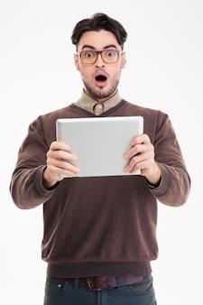 Portret zszokowanego mężczyzny korzystającego z komputera typu tablet na białej ścianie