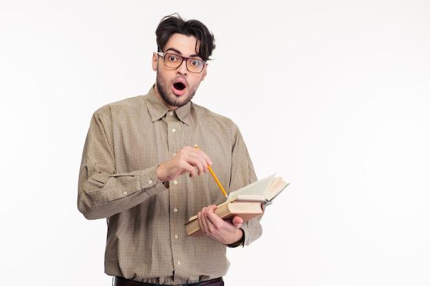 Portret zszokowanego mężczyzny stojącego z książką na białym tle na białej ścianie