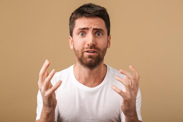 Portret zszokowanego młodego mężczyzny niedbale ubranego stojącego na białym tle nad beżem, gestykuluje