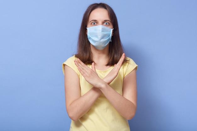 Portret zszokowanego, przestraszonego ślicznego modelu krzyżującego ramiona, odmawiającego, protestującego, trzymającego się zasad izolacji, utrzymującego dystans, noszącego maskę i koszulkę, szeroko otwierającego oczy. koncepcja koronawirusa.