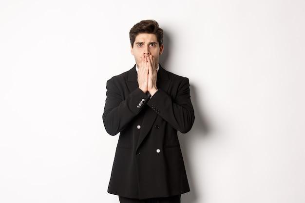 Portret zszokowanego przystojnego biznesmena w garniturze, reagującego na straszną sytuację, dyszącego i zakrywającego usta rękami, stojącego zaskoczonego na białym tle