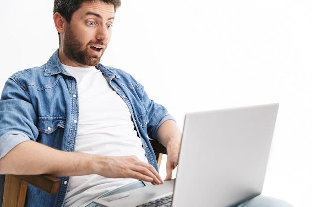 Portret zszokowanego, przystojnego brodatego mężczyzny w zwykłych ubraniach, siedzącego na krześle na białym tle nad białą ścianą, pracującego na laptopie